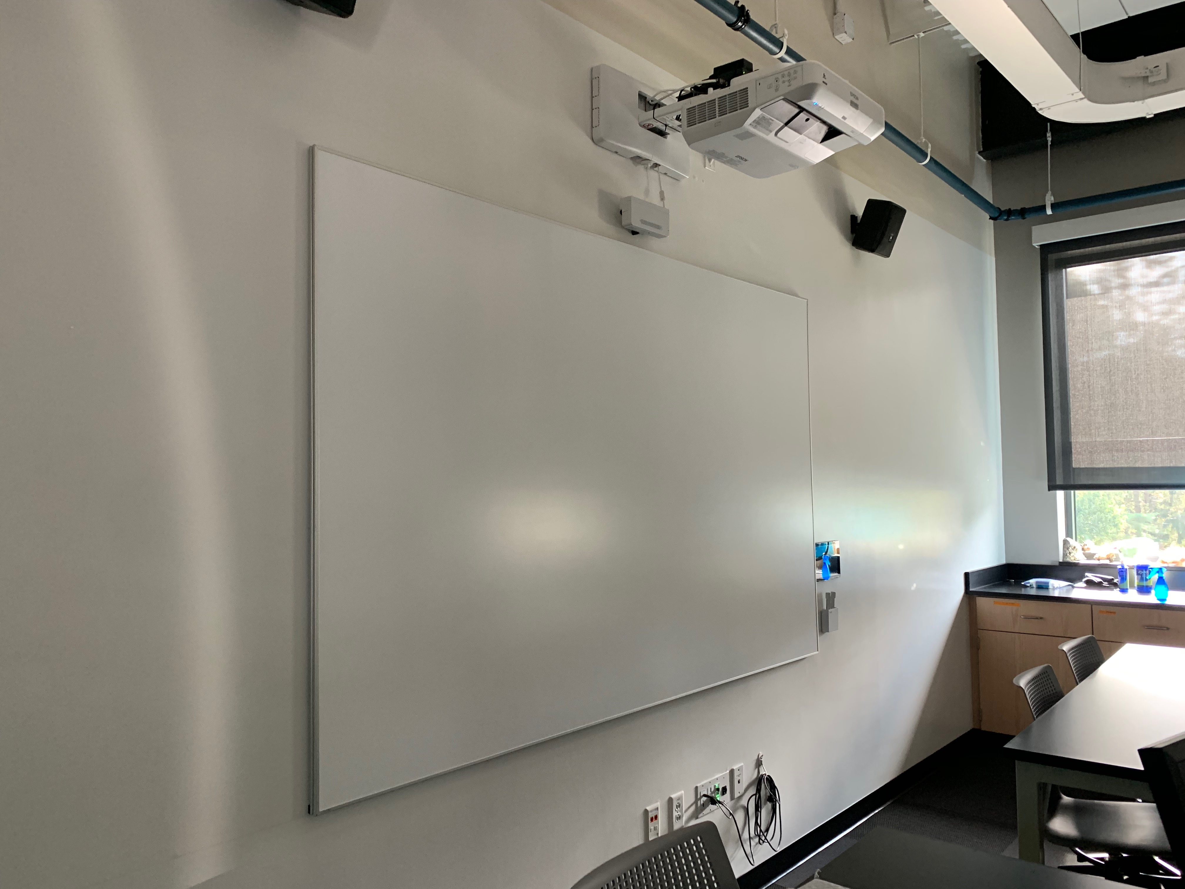 Roux 303 looking at the whiteboard wall and projection surface with interactive projector